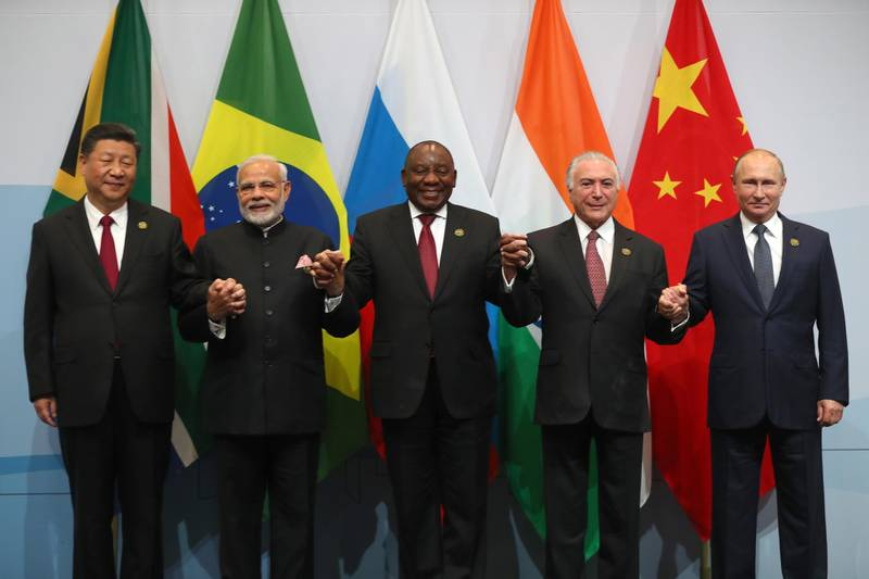 epa06911010 China's President Xi Jinping (L) India Prime Minister Narendra Modi (2-L) South Africa's President Cyril Ramaphosa (C) Brazil President Michel Temer (2-R) and President Vladimir Putin (R), hold hands during the BRICS Summit 'family photo' held in Johannesburg, South Africa, 26 July 2018. The summit is held over three days and ends on 27 July.  EPA/MIKE HTUCHINGS / POOL