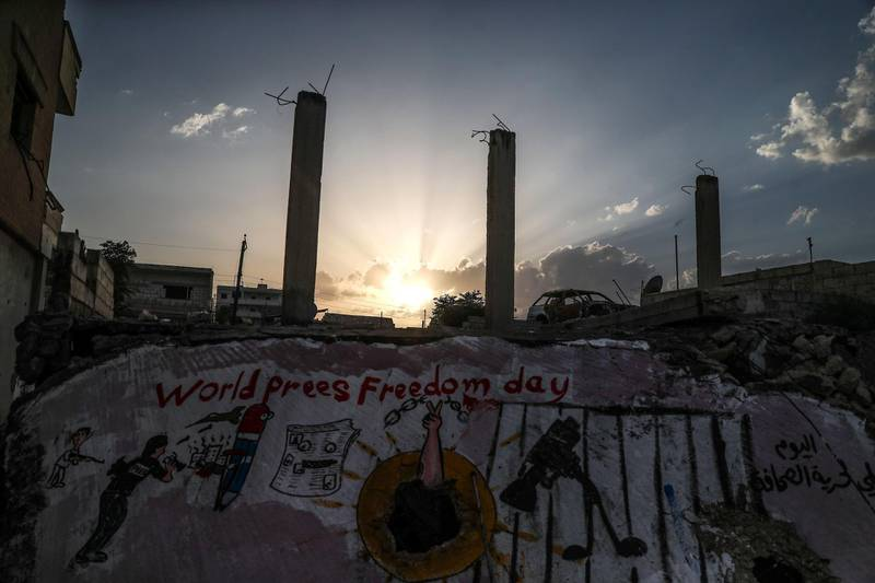 epa06715388 The sun sets over a new graffiti by Azeez al-Asmer, Binnish Town, Idlib, Northern Syria, 05 May 2018 (Issued 06 May 2018). Azeez al-Asmer, a 45-years-old Syrian graffiti artist who paints graffiti and murals on the walls of the town of Binnish in northern Syria since 2013. His work is usually sarcastic and reflects on events regarding the Syrian conflict.  EPA/MOHAMMED BADRA