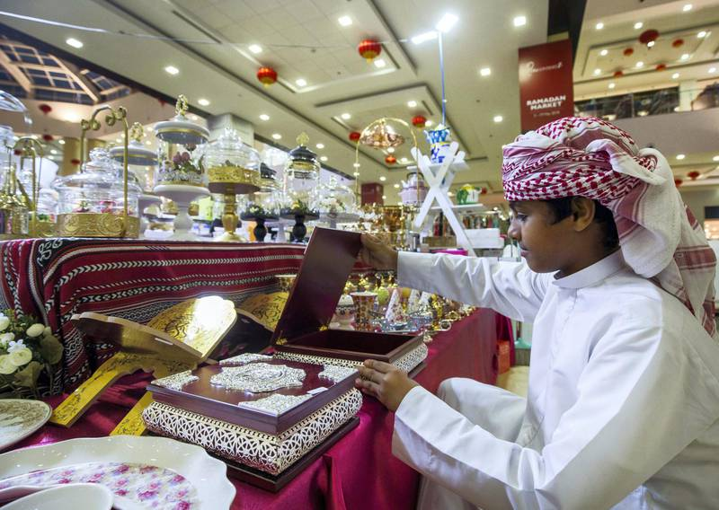 DUBAI, UNITED ARAB EMIRATES, 04 May 2018 - A boy checking out different items at Ramadan Market, Dragon Mart 2.  Leslie Pableo for The National for Ellen Fortini's story