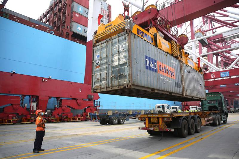 A worker wearing a face mask to protect against the new coronavirus guides the loading of a shipping container at a container port in Qingdao in eastern China's Shandong Province, Thursday, July 9, 2020. China's imports of U.S. goods rose 10.6% in June over a year earlier and its global trade also increased in a fresh sign the world's second-largest economy is gradually recovering from the coronavirus pandemic, customs data showed Tuesday July 14, 2020. (Chinatopix via AP)
