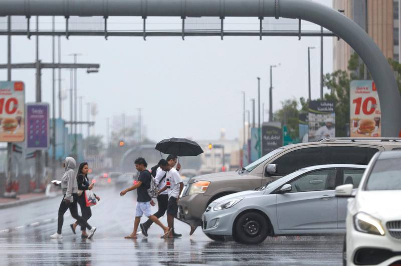 Abu Dhabi, United Arab Emirates, November 20, 2019.    UAE weather: rainfall and storms arrive at downtown Abu Dhabi. --  Abu Dhabi residents cross the intersection of Hazza Bin Zayed The First St. and Sultan Bin Zayed The First St. during a rain shower. Victor Besa / The National Section:  NA Reporter: