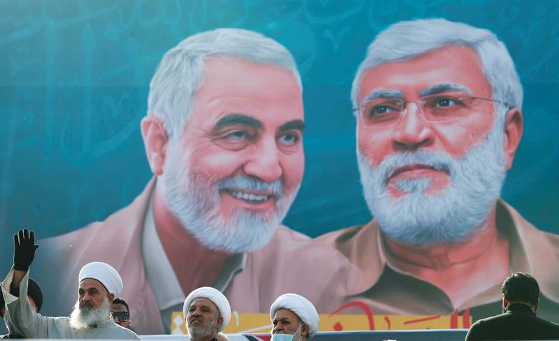 Iraqi clerics look on as they stand near a banner depicting senior Iranian military commander General Qassem Soleimani and Iraqi militia commander Abu Mahdi al-Muhandis, during a gathering marking the one year anniversary of their killing in a U.S. attack, in Baghdad, Iraq January 3, 2021. REUTERS/Thaier Al-Sudani