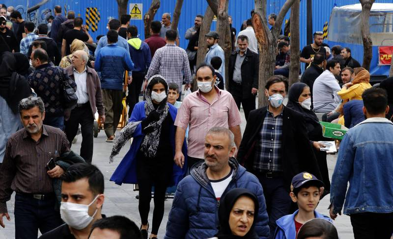 Iranians, some wearing protective masks, gather inside the capital Tehran's grand bazaar, during the Covid-19 coronavirus pandemic crises, on March 18, 2020. Iran said its novel coronavirus death toll surpassed 1,000 today as President Hassan Rouhani defended the response of his administration, which has yet to impose a lockdown. The COVID-19 outbreak in sanctions-hit Iran is one of the deadliest outside China, where the disease originated.  / AFP / -