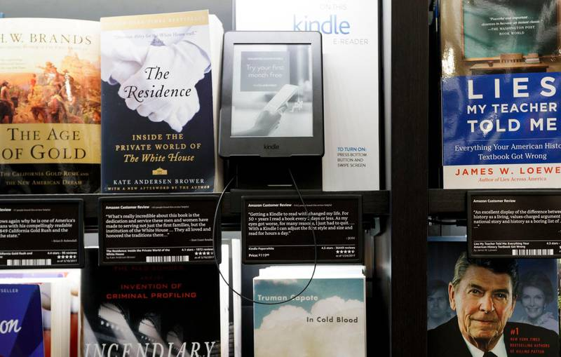 epa05990107 An Amazon Kindle device (C) is displayed on a shelf next to real books at the newly opened Amazon Books store in Columbus Circle in New York, New York, USA, 25 May 2017. The store, which sells books and is a way for the company to promote its brand, is the Amazon's first in New York City, and its seventh in the country.  EPA/JUSTIN LANE