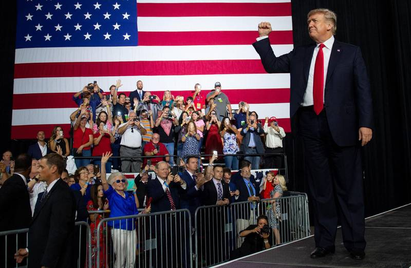 TOPSHOT - US President Donald Trump greets the crowd during a campaign rally at the Florida State Fairgrounds Expo Hall in Tampa, Florida, on July 31, 2018. / AFP PHOTO / SAUL LOEB