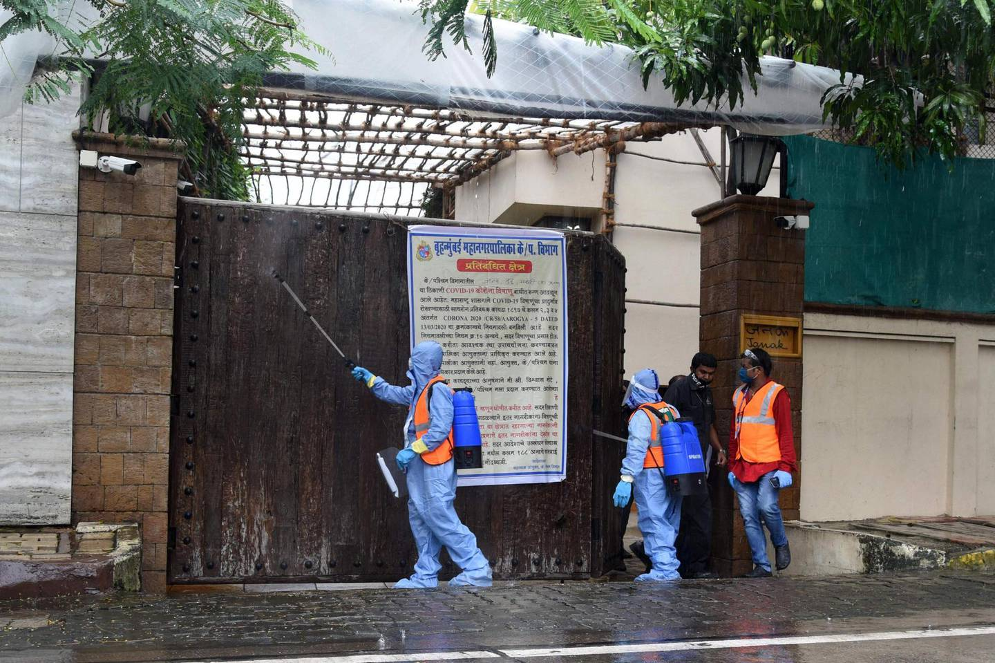 Civic authority workers spray sanitiser on the main door of the residence of Bollywood star Amitabh Bachchan as he tested positive for COVID-19 in Mumbai on July 12, 2020. Bollywood megastar Amitabh Bachchan, 77, tested positive for COVID-19 on July 11 and was admitted to hospital in Mumbai, with his actor son Abhishek -- who also announced he had the virus -- saying both cases were mild. / AFP / Sujit Jaiswal