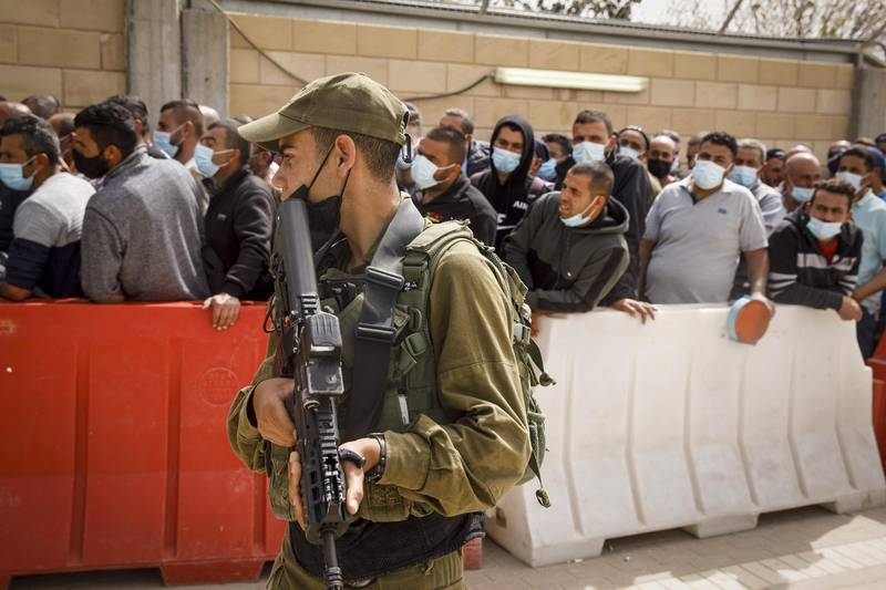 An armed Israeli soldier stands guard as Palestinian laborers wait in line to receive a dose of the Moderna Inc. Covid-19 vaccine at a temporary vaccination center at the Meitar checkpoint crossing into Israel, south of Hebron, West Bank, on Tuesday, March 9, 2021. Israel started to vaccinate Palestinian laborers who work inside its borders and in West Bank settlements on Monday, in a boost for Israeli builders and the Palestinian economy. Photographer: Kobi Wolf/Bloomberg