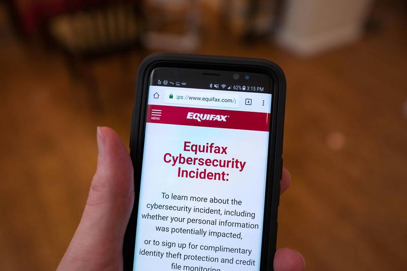 """Close-up of the hand of a man holding a mobile phone open to the web site of credit bureau Equifax, with text on the website reading """"Equifax Cybersecurity Incident"""", providing steps for consumers to take following a security breach at the company, San Ramon, California, September 28, 2017. (Photo by Smith Collection/Gado/Getty Images)"""