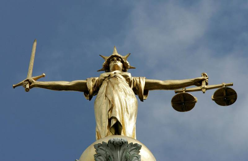 FILE PHOTO: The Statue of Justice is seen on top of the London Central Criminal Court, the Old Bailey, in London August 12, 2005./File Photo