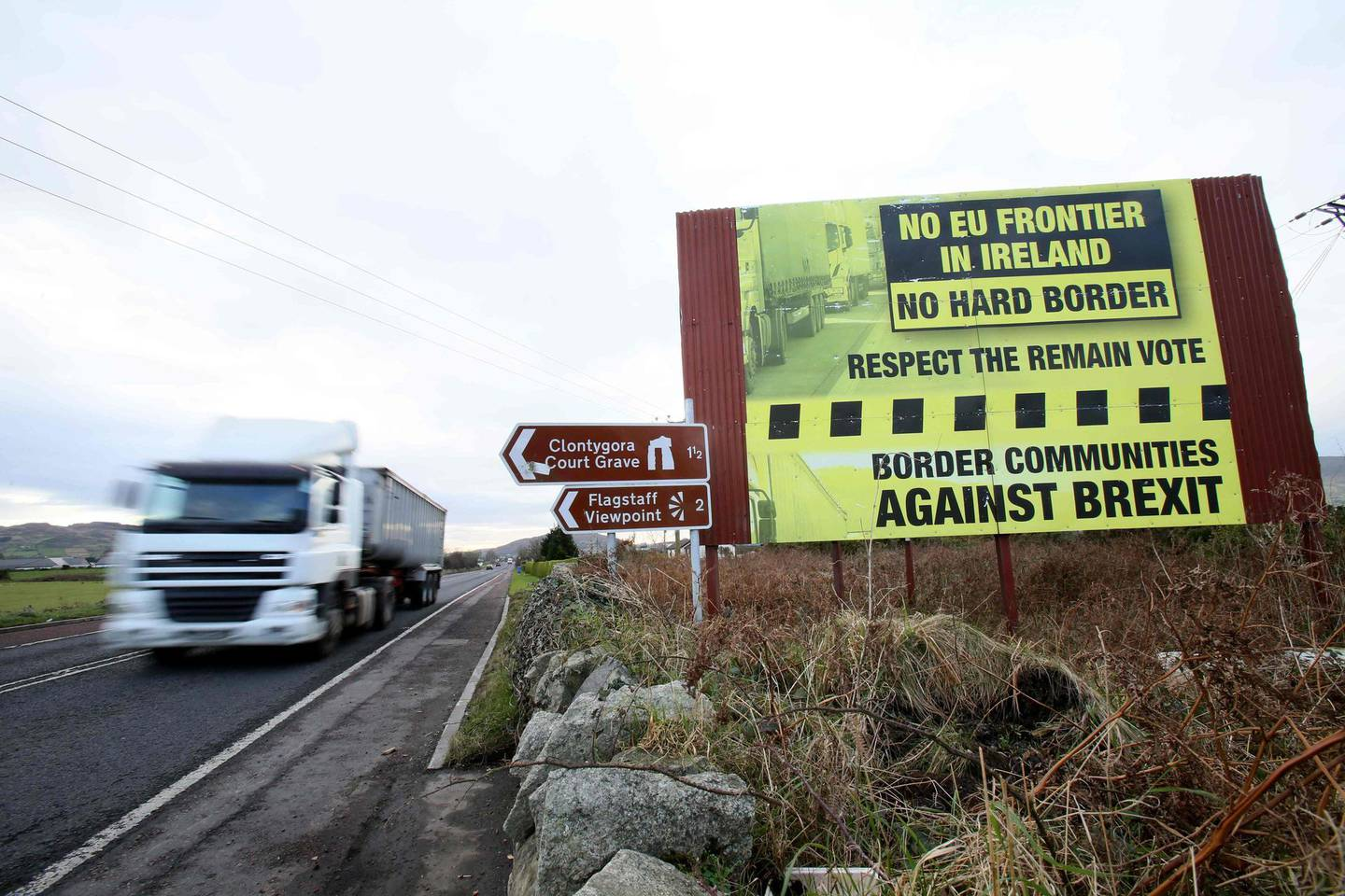 Traffic crosses the border into Northern Ireland from the Irish Republic alongside a Brexit Border poster on the Dublin road Co Armagh border, between Newry in Northern Ireland and Dundalk in the Irish Republic, on December 1, 2017,   The European Union will not accept Britain's  Brexit offer if Ireland is not satisfied with proposals for future border arrangements, EU President Donald Tusk said in Dublin on December 1, 2017. / AFP PHOTO / Paul FAITH