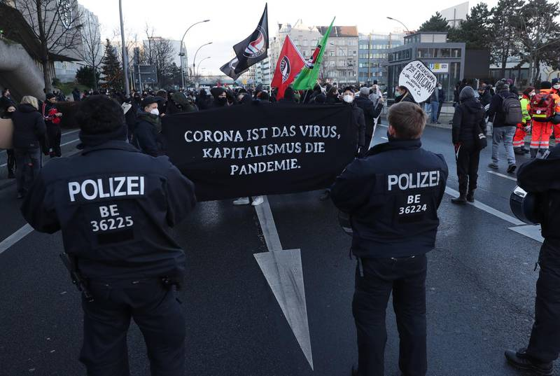 epa08911336 People holding a placard reading 'Corona is the virus, capitalism is the pandemic' during a demonstration 'FCK2020 - For a better tomorrow' in Berlin, Germany, 30 December 2020. Protesters are against coronavirus conspiracy ideologues and for dignified health, a fair education, labor rights and labor protection.  EPA/HAYOUNG JEON