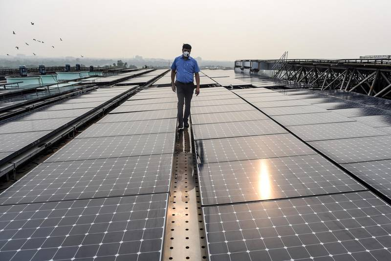 In this photograph taken on July 17, 2020, an employee walks among solar panels installed on the building of Indira Paryavaran Bhawan or the Indian Environment Ministry in New Delhi. (Photo by Money SHARMA / AFP)