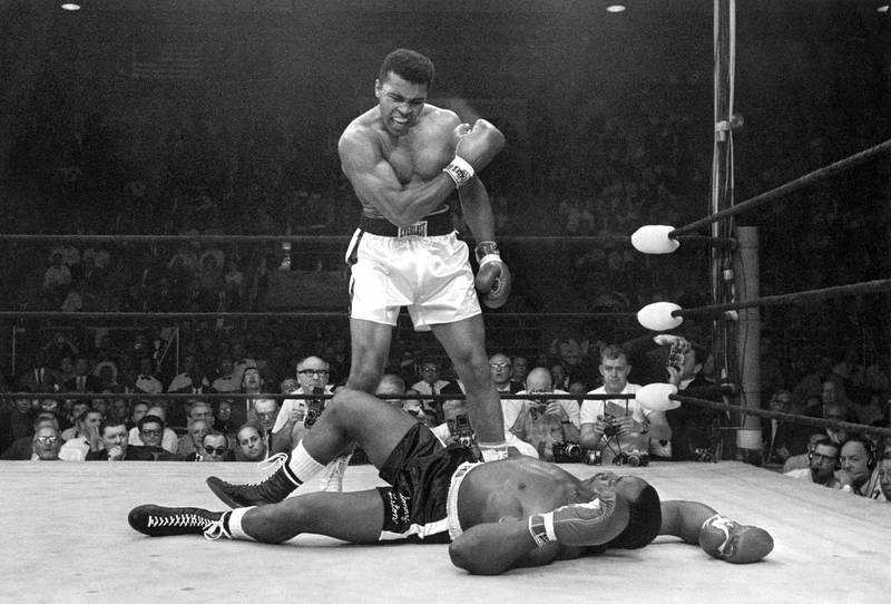 FILE - In this May 25, 1965 file photo, heavyweight champion Muhammad Ali stands over fallen challenger Sonny Liston, shouting and gesturing shortly after dropping Liston with a short hard right to the jaw, in Lewiston, Maine. The bout lasted only one minute into the first round. Ali is the only man ever to win the world heavyweight boxing championship three times. He also won a gold medal in the light-heavyweight division at the 1960 Summer Olympic Games in Rome as a member of the U.S. Olympic boxing team. In 1964 he dropped the name Cassius Clay and adopted the Muslim name Muhammad Ali. (AP Photo/John Rooney, File)