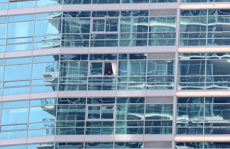 DUBAI, UNITED ARAB EMIRATES , April 17– 2020 :- One of the resident looks out from his apartment in Dubai Marina in Dubai. Dubai is conducting 24 hours sterilisation programme across all areas and communities in the Emirate and told residents to stay at home. UAE government told residents to wear face mask and gloves all the times outside the home whether they are showing symptoms of Covid-19 or not.  (Pawan Singh / The National) For News/Online/Instagram