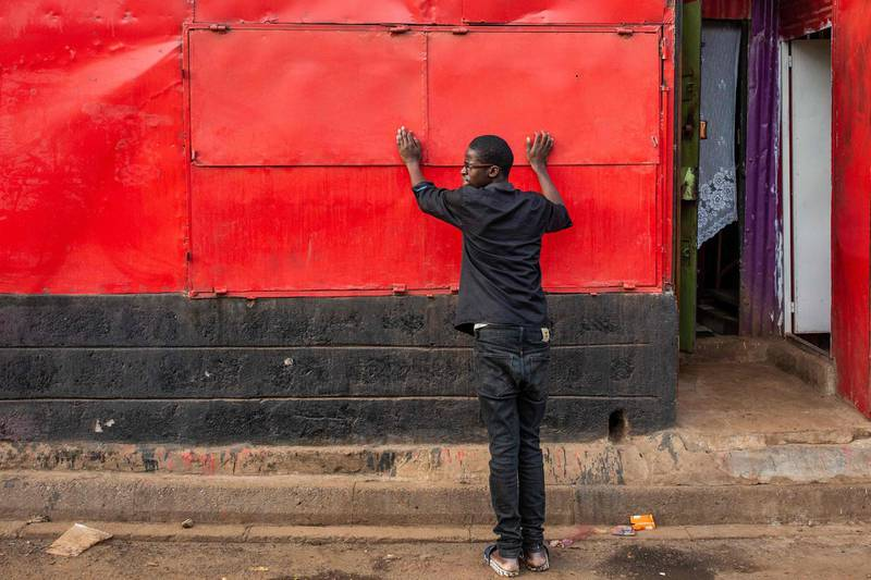 A man closes his business before the beginning of a curfew which was ordered by Kenyan President, Uhuru Kenyatta, to contain the spread of the COVID-19 coronavirus on March 27, 2020 in Kibera, Nairobi. Kenyan President Uhuru Kenyatta on March 25, 2020, ordered a nighttime curfew to curb the spread of the COVID-19 coronavirus, while taking a massive pay cut and unveiling tax breaks to ease the economic impact of the crisis on citizens. / AFP / patrick meinhardt