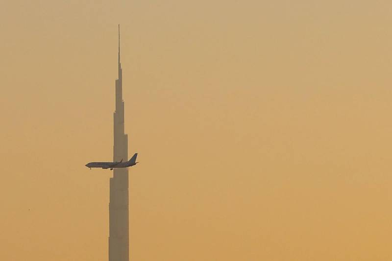 A commercial airplane flies past Burj Khalifa as it starts landing at Dubai international airport in the United Arab Emirates, on January 9, 2021. / AFP / GIUSEPPE CACACE
