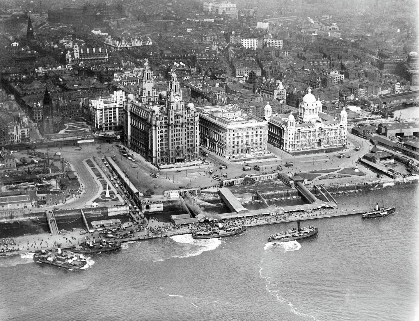 George's Landing Stage and the Three Graces, Liverpool, Merseyside, 1920. A number of vessels plying their trade on the River Mersey. The 'Three Graces' are the Royal Liver Building (completed in 1911 with two clock towers crowned by mythical Liver Birds), the Cunard Building (completed in 1916) and the Port of Liverpool Building (completed in 1907). The landing stage at Pier Head served the transatlantic liner service. Artist Aerofilms. (Photo by English Heritage/Heritage Images/Getty Images)
