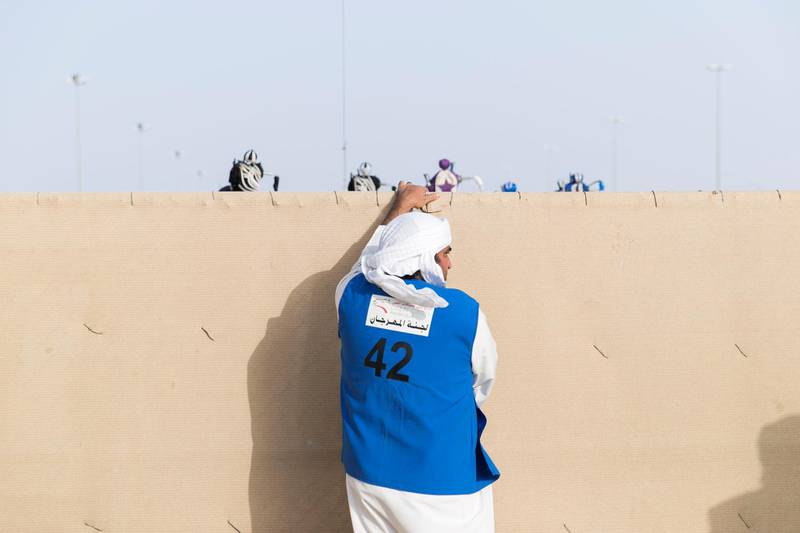 DUBAI, UNITED ARAB EMIRATES - Feb 15, 2018.  A man closes the gate at the start line of Al Marmoum Race Track.  The fastest camels in the Gulf will compete for cash, swords, rifles and luxury vehicles totalling Dh95 million at the first annual Sheikh Hamdan Bin Mohammed Bin Rashid Al Maktoum Camel Race Festival in Dubai.   (Photo: Reem Mohammed/ The National)  Reporter: Section: NA