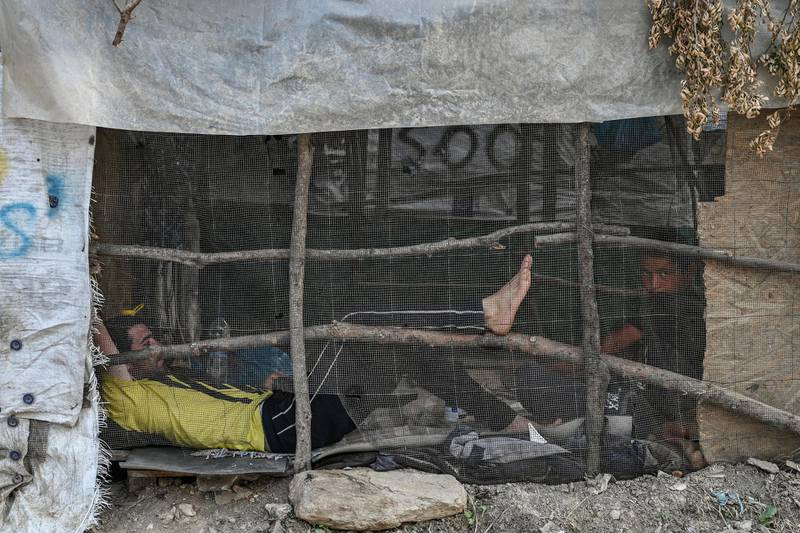 A man lying down in a improvised tents camp near the refugee camp of Moria in the island of Lesbos on June 21, 2020. - Greece's announcement that it was extending the coronavirus lockdown at its migrant camps until July 5, cancelling plans to lift the measures on June 22, coincided with World Refugee Day on June 27, 2020. (Photo by ARIS MESSINIS / AFP)