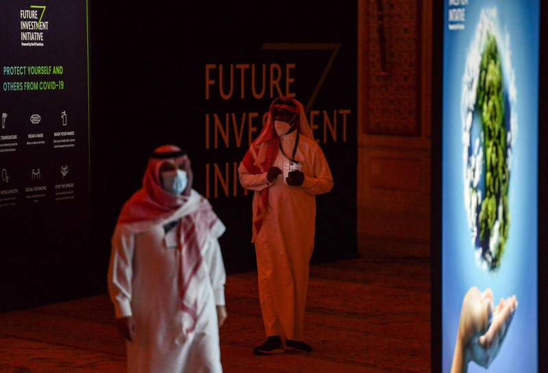 Delegates walk during the fourth edition of the Future Investment Initiative (FII) conference at the capital Riyadh's Ritz-Carlton hotel on January 27, 2021. Saudi Arabia opened a two-day Davos-style investment forum, with dozens of global policy makers and business tycoons lined up to speak at the largely virtual event amid the coronavirus pandemic. Only 200 of around 8,000 registered delegates attended in-person, while around 100 speakers are set to participate virtually with 50 present physically. Previous summits drew thousands of Wall Street titans and global policymakers. / AFP / FAYEZ NURELDINE