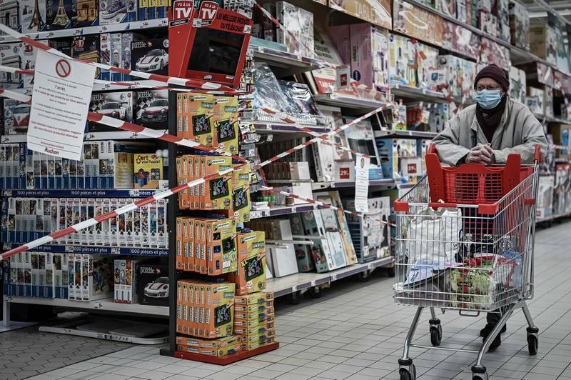 """TOPSHOT - A customer pushes a trolley past the closed toy department of a supermarket in Bordeaux on November 4, 2020, on the sixth day of a lockdown aimed at containing the spread of the novel coronavirus (Covid-19). Supermarkets banned on November 4, 2020 the sale of """"non-essential products"""", a measure taken by the government following a restriction first imposed in response to the health crisis. / AFP / Philippe LOPEZ"""