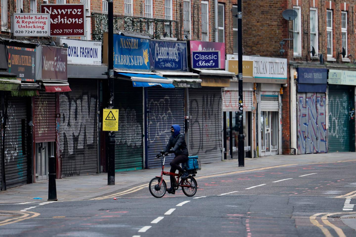 A delivery man cycles past shuttered shops along a near-deserted street in the City of London on January 15, 2021, during the third coronavirus lockdown. Britain's economy slumped 2.6 percent in November on coronavirus restrictions, official data showed January 15, 2021, stoking fears that the current virus lockdown could spark a double-dip recession. / AFP / Tolga Akmen