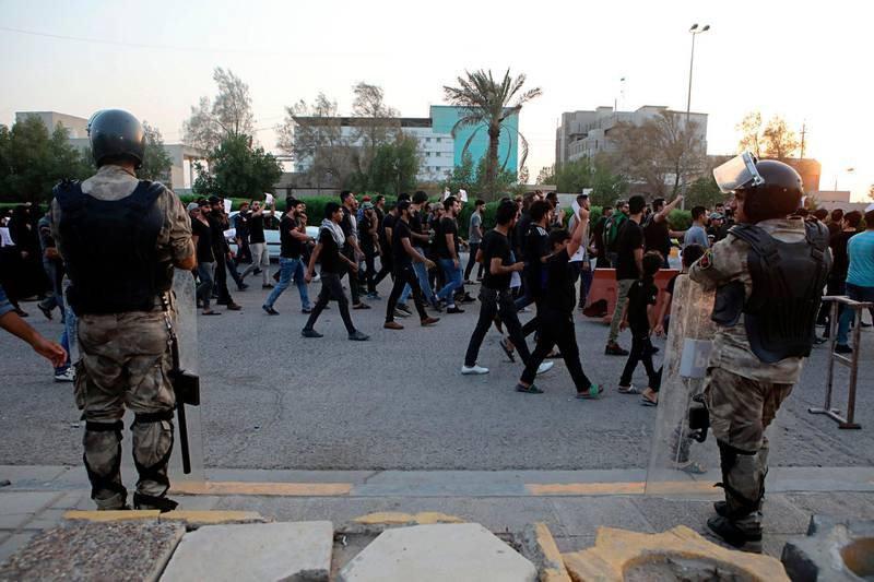 Iraqi riot police stand guard while demonstrators gather outside Basra police directorate demanding the release of detained protesters in Basra, 340 miles (550 km) southeast of Baghdad, Iraq, Sunday, Sept. 16, 2018. (AP Photo/Nabil al-Jurani)