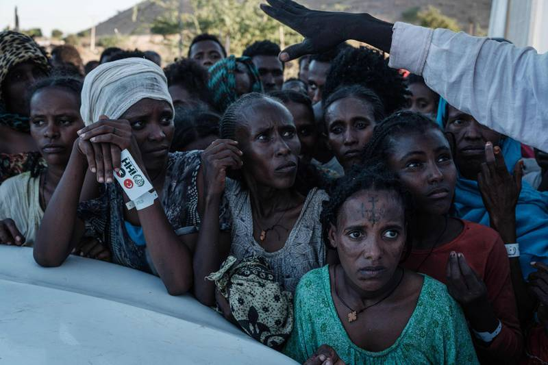 TOPSHOT - Ehiopians, who fled the Ethiopia's Tigray conflict as refugees, wait for food distribution in front of a warehouse at Um Raquba refugee camp in Gedaref, eastern Sudan, on December 1, 2020.  More than 45,000 people have escaped from northern Ethiopia since November 4, after Prime Minister Abiy Ahmed ordered military operations against leaders of Tigray's ruling party in response to its alleged attacks on federal army camps. / AFP / Yasuyoshi CHIBA