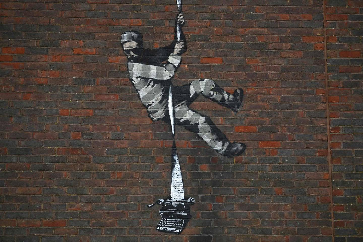 (FILES) This file photo taken on March 02, 2021 shows an artwork by street artist Banksy on the side of Reading Prison in Reading, west of London.  Street artist Banksy on March 4 claimed responsibility for a painting on the wall of a former British prison that once held playwright Oscar Wilde. The artwork shows a prisoner escaping on a rope made of bedsheets tied to a typewriter.  - RESTRICTED TO EDITORIAL USE - MANDATORY MENTION OF THE ARTIST UPON PUBLICATION - TO ILLUSTRATE THE EVENT AS SPECIFIED IN THE CAPTION  / AFP / BEN STANSALL / RESTRICTED TO EDITORIAL USE - MANDATORY MENTION OF THE ARTIST UPON PUBLICATION - TO ILLUSTRATE THE EVENT AS SPECIFIED IN THE CAPTION