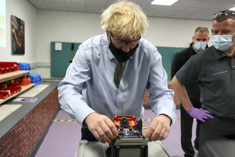 """Britain's Prime Minister Boris Johnson (L) tries his hand at cable splicing with instructor Colin Wilkinson (R) during a visit to the Openreach Learning and Development Training Centre in Bolton, Greater Manchester, northwest England, on December 18, 2020.  Openreach, a division of British telecoms giant BT, announced December 18 plans for 2,500 new engineering jobs across the UK next year as it upgrades broadband services. Meanwhile, as EU and UK negotiators continued to lock horns Britain said on December 17 it was """"very likely"""" a Brexit trade deal would not be secured without a significant shift from Brussels. / AFP / POOL / Peter Byrne"""