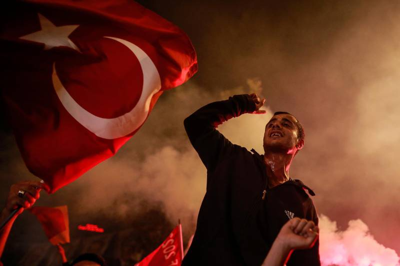 In this photo taken late Sunday, June 24, 2018, a supporter of Turkey's President and ruling Justice and Development Party, or AKP, leader Recep Tayyip Erdogan, chants slogans during celebrations outside the party headquarters in Istanbul. According to unofficial results, Erdogan won 52.6 percent of the votes in the presidential race, avoiding a second-round runoff vote. His ruling Justice and Development Party garnered 42.5 percent of the parliamentary vote. (AP Photo/Emrah Gurel)