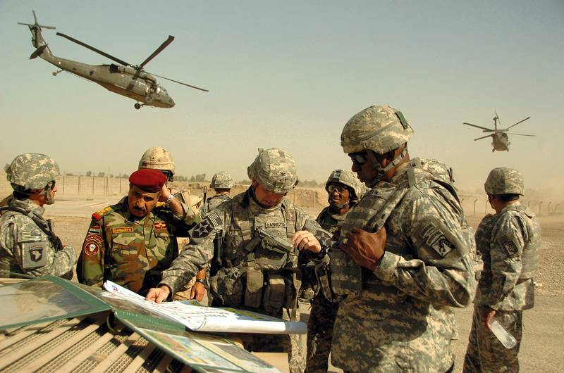 """A picture released by the US military shows US army Lt. General Lloyd J. Austin III (R), commander of the XVIII Airborne Corps, Col. Jeffrey L. Bannister (C), commander of the 2nd Infantry Brigade Combat Team and Iraqi Brigadier General Abdulah (L), discussing troop progress during a field meeting outside Baghdad, Iraq, 11 September 2007. Iraqi special forces backed by US troops launched a raid 25 September 2007 against Iraq's largest military academy detaining """"20 criminals"""". AFP PHOTO/ Spc. Nicholas A. Hernandez/US Army (Photo by SPC NICHOLAS HERNANDEZ / DOD / AFP)"""