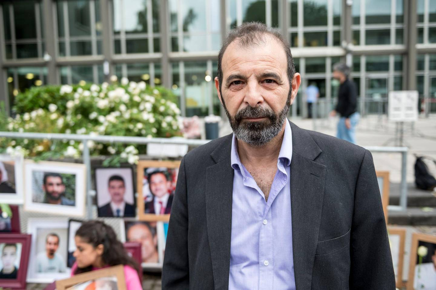 Syrian human rights lawyer Anwar al-Bunni, speaks to the media in front of pictures of victims of the Syrian regime, during a protest outside the trial against two Syrian alleged former intelligence officers accused for crimes against humanity, in the first trial of its kind to emerge from the Syrian conflict, on June 4, 2020 in Koblenz, western Germany. (Photo by Thomas Lohnes / AFP)