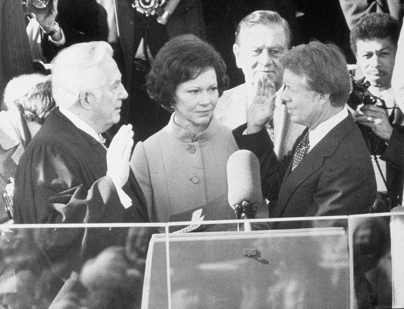 Democrat Jimmy Carter is sworn in by chief justice Earl Burger as the 39th president of the United States while first lady Rosalynn looks on, Washington DC, January 20, 1977. (Photo by Hulton Archive/Getty Images)