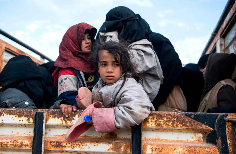 TOPSHOT - Civilians who fled from the embattled Baghouz area in the eastern Syrian province of Deir Ezzor sit in a truck on February 14, 2019 during an operation by the US-backed Syrian Democratic Forces (SDF) to expel hundreds of Islamic State group (IS) jihadists from the region.  / AFP / Fadel SENNA