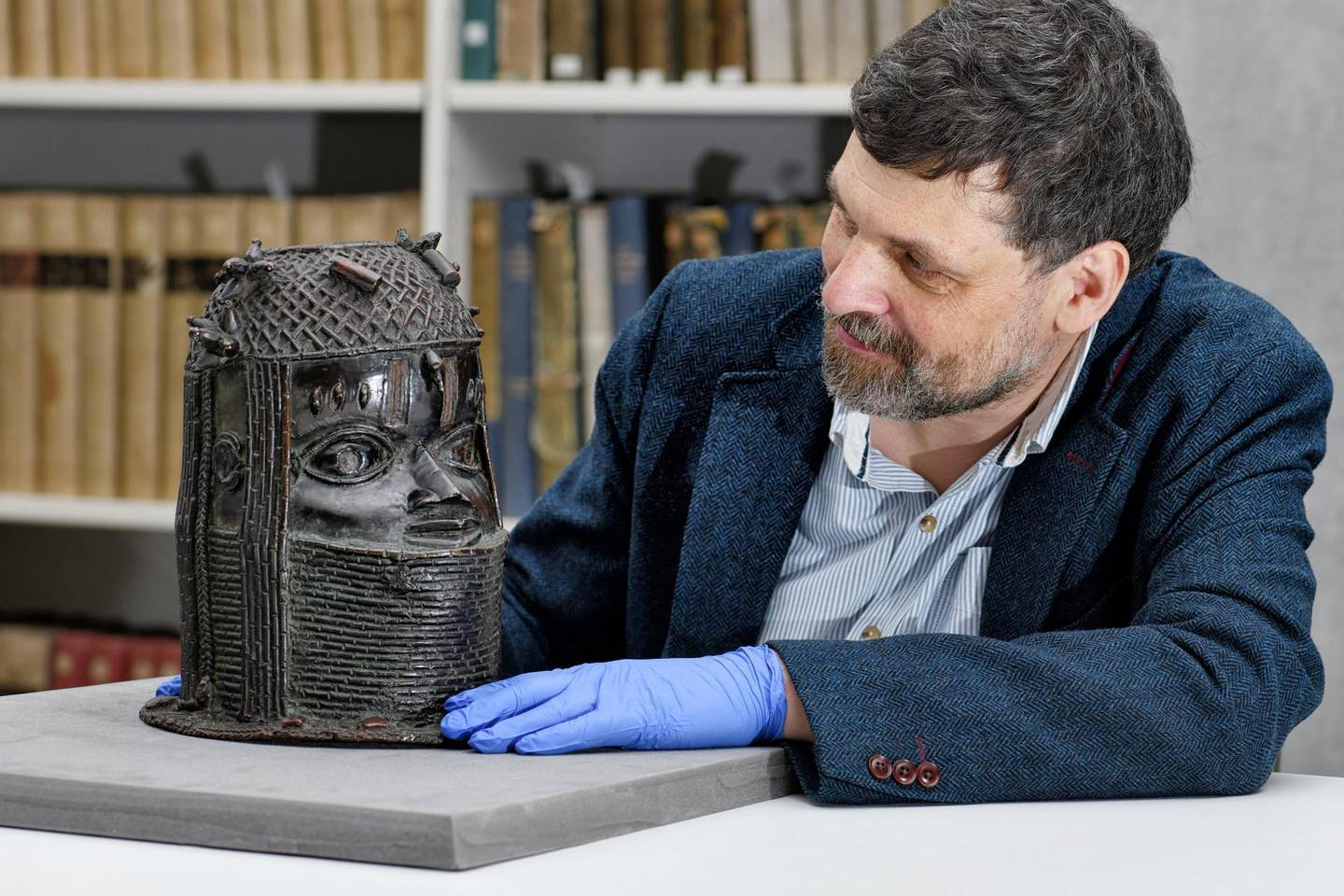 Neil Curtis, Head of Museums and Special collections is seen with one of the Benin bronze depicting the Oba of Benin at The Sir Duncan Rice Library, the University of Aberdeen, in Aberdeen, Scotland, Britain March 17, 2021. Picture taken March 17, 2021. University of Aberdeen/Handout via REUTERS  THIS IMAGE HAS BEEN SUPPLIED BY A THIRD PARTY. MANDATORY CREDIT. NO RESALES. NO ARCHIVES.