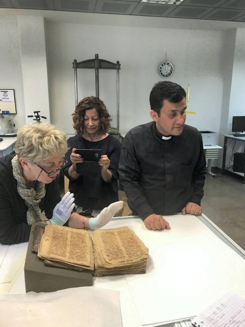 Father Ammar Altony Yako  with the historic Aramaic prayer manuscript. Courtesy Father Ammar Altony Yako