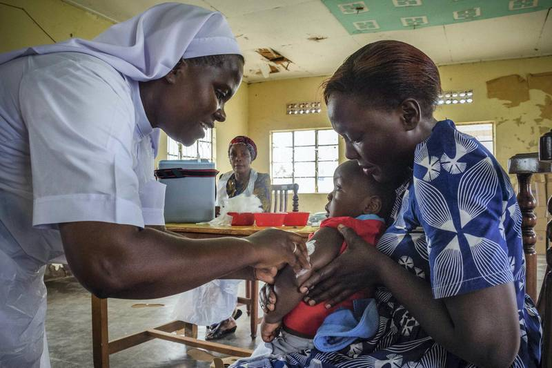 A child reacts as he receives an injection during the nationwide vaccination campaign against measles, rubella and polio targeting all children under 15 years old in Nkozi town, about 84 km from the capital Kampala, on October 19, 2019. - Uganda's Ministry of health with WHO and UNICEF aim to immunize more than 18 million children in Uganda which is about 43 percent of the population during their 5-day vaccination campaign. (Photo by Badru KATUMBA / AFP)