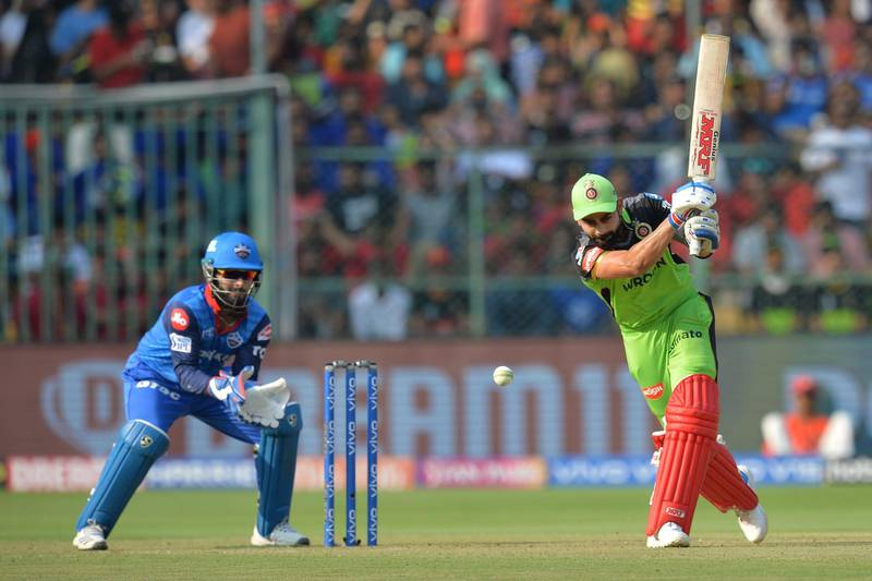 Royal Challengers Bangalore batsman and captain Virat Kohli (R) plays a shot while Delhi Capitals wicketkeeper Rishab Pant looks on during the 2019 Indian Premier League (IPL) Twenty20 cricket match between Royal Challengers Bangalore and Delhi Capitals at The M. Chinnaswamy Stadium in Bangalore on April 7, 2019. (Photo by Manjunath KIRAN / AFP) / ----IMAGE RESTRICTED TO EDITORIAL USE - STRICTLY NO COMMERCIAL USE-----