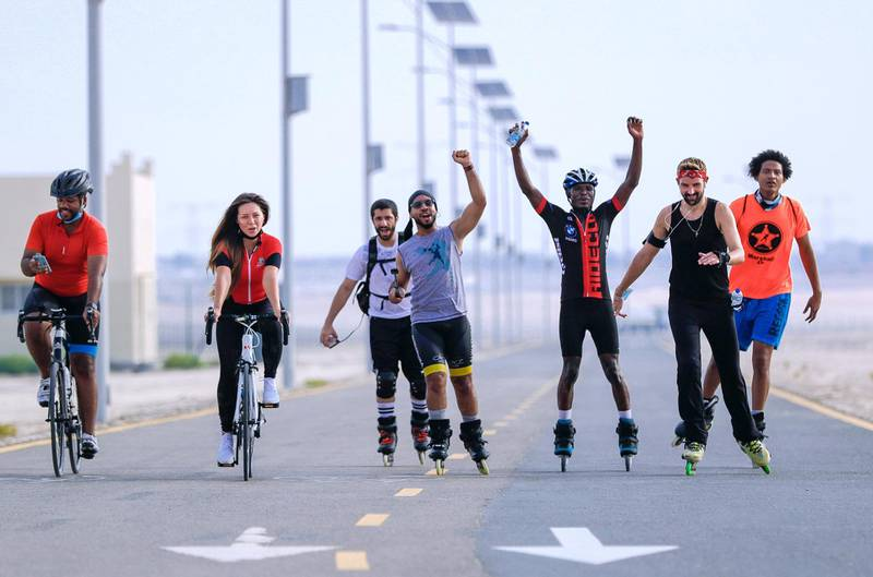 Abu Dhabi, United Arab Emirates, August 21, 2020.   The Madrollers skating group at the Al Wathba Bicycle Track do a  8 km. fun sprint.  The skating group has members from Dubai and Abu Dhabi.  They encourage safety and discipline on roller-skates, skateboard, long-board and bicycles.  --  Veteran rollerbladers go back a few kilometers to cheer on Chief Benard (second from right), one of the novice skaters of the group who got left behind.  Victor Besa /The NationalSection:  Photo ProjectReporter: