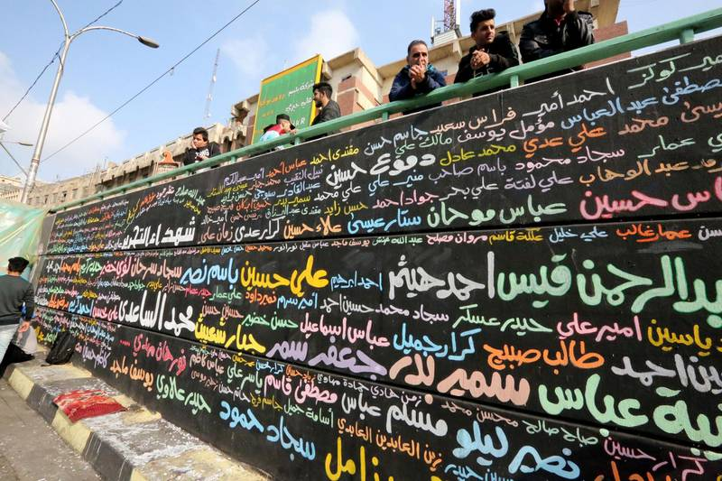 A memorial mural bearing names of demonstrators killed during ongoing anti-government protests is seen in Tahrir square in the capital Baghdad on December 8, 2019. Thousands attended angry protests in Baghdad and southern Iraq today, grieving but defiant after 20 of them were killed in an attack the previous day, in dramatic developments which threaten to derail the anti-government rallies rocking Iraq since October, the largest and deadliest grassroots movement in decades. / AFP / SABAH ARAR