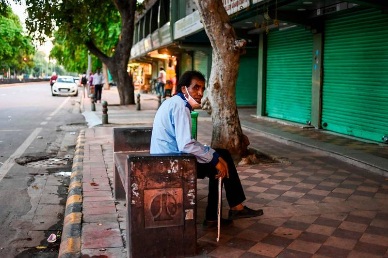 A security guard rests sitting on a bench in front of a row of closed shops in New Delhi on August 31, 2020. / AFP / Jewel SAMAD