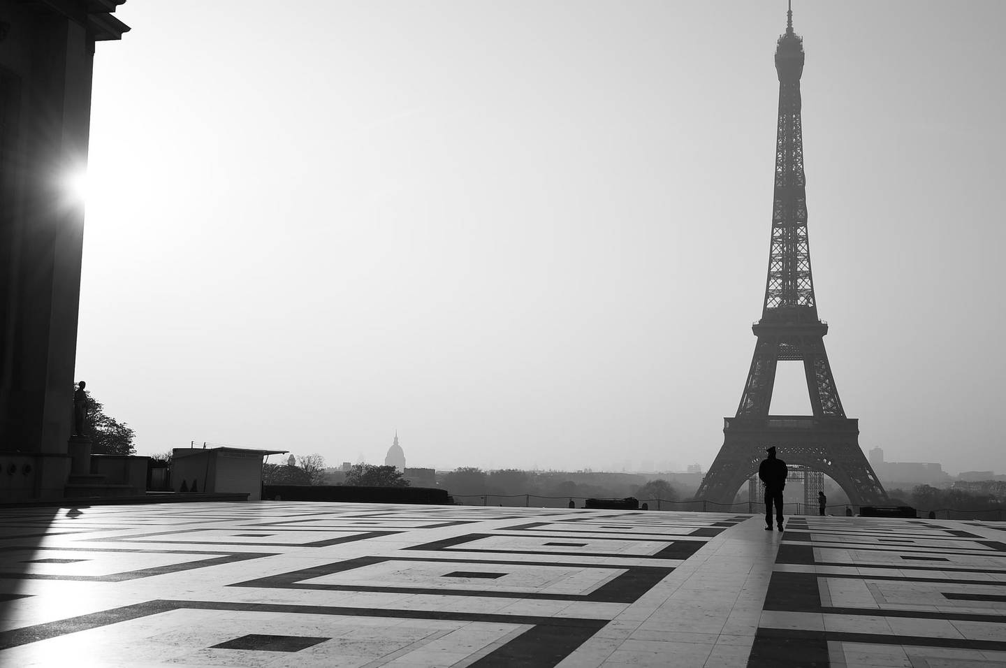 PARIS, FRANCE - MARCH 28: EDITORS NOTE : (This image has been converted to Black and White). A police officer walks on Trocadero square with the Eiffel tower in the background on March 28, 2020 in Paris, France. The country has introduced fines for people caught violating its nationwide lockdown measures intended to stop the spread of COVID-19. The pandemic has spread to at least 182 countries, claiming over 30,000 lives and infecting hundreds of thousands more. (Photo by Pascal Le Segretain/Getty Images)