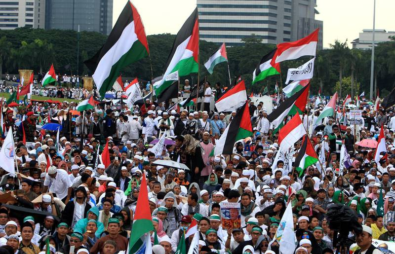 epa06394628 Indonesian muslim activists hold placards and wave Palestine national flags during a protest against US President Donald J.Trump's decision to recognize Jerusalem as capital of Israel at the National Mounement in Jakarta, Indonesia, 17 December 2017. On 06 December, US president Donald J. Trump announced he is recognising Jerusalem as the capital of Israel and will relocate the US embassy from Tel Aviv to Jerusalem.  EPA/ADI WEDA