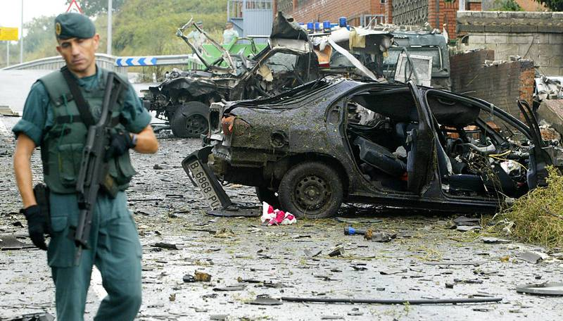 """(FILES) In this file photo taken on August 24, 2007 civil guards inspect car bomb wreckage that exploded outside the barracks of Spain's paramilitary Guardia Civil in the northern town of Durango in the Basque region. The Basque separatist group ETA apologised on April 20, 2018 for the """"pain"""" and """"harm"""" it caused during its decades-long campaign of violence, and appealed to its victims for forgiveness. The statement came just days before ETA is expected to announce its dissolution.     / AFP PHOTO / Rafa RIVAS"""