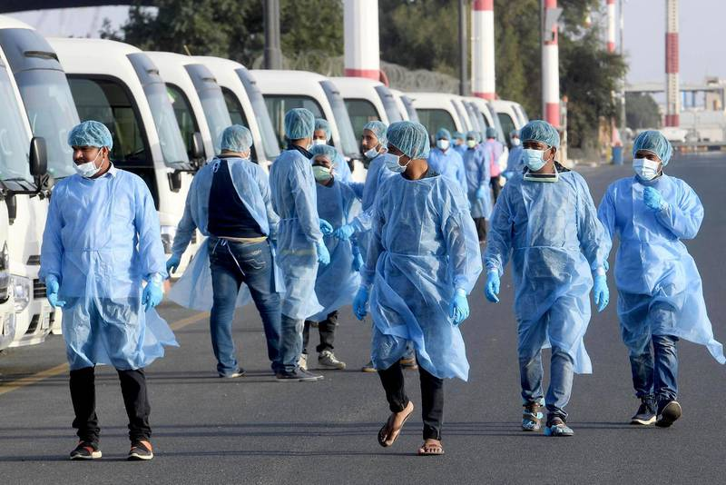 Health ministry workers, wearing protective outfits, wait on the tarmac of the Kuwait international Airportat to receive Kuwaitis returning from Frankfurt on March 26, 2020, to be taken to a hospital for novel coronavirus checkups, in the capital Kuwait City.  / AFP / STR