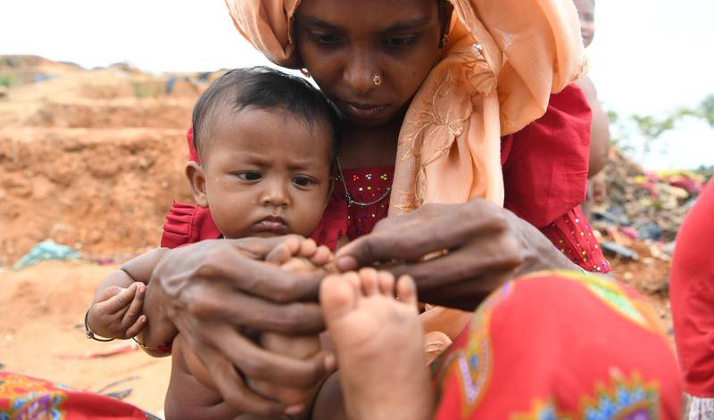 """A Rohingya refugee mother uses a blade to cut the overgrown nails of her child at the Palangkhali refugee camp in Ukhia district on October 12, 2017. Bangladesh has heavily curtailed access to the Rohingya camps in recent years, but eased restrictions last month after more than 520,000 new refugees poured across the border. The government's NGO Affairs Bureau approved 30 local and global aid groups to meet """"emergency needs"""" in the overwhelmed camps, which already housed about 300,000 Rohingya before the latest influx.  / AFP PHOTO / INDRANIL MUKHERJEE"""