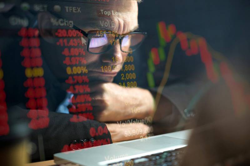 Businessman checking stock market data on computer screen and contemplating