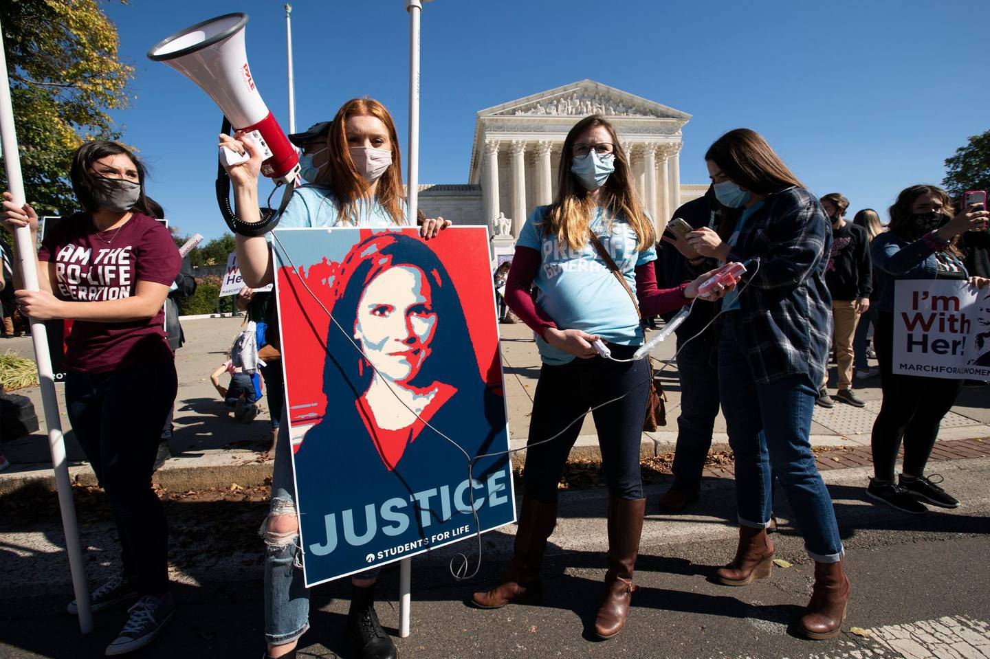 Supporters of Supreme Court nominee Amy Coney Barrett rally outside the Supreme Court building during the Women's March in Washington, Saturday, Oct. 17, 2020. (AP Photo/Jose Luis Magana)