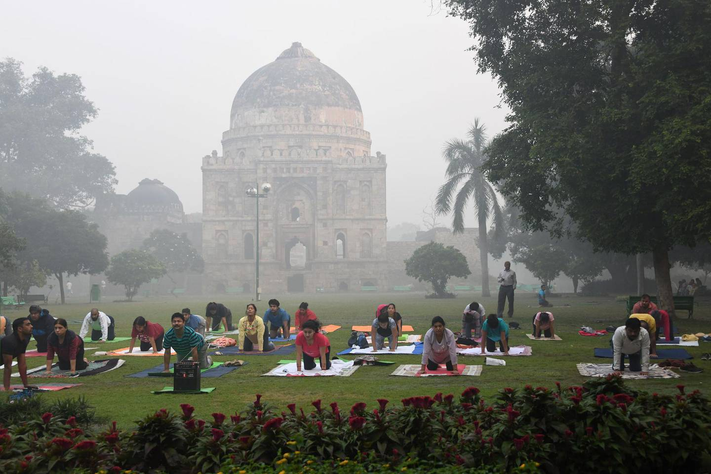 (FILES) In this file photo taken on October 30, 2018 Indian yoga enthusiasts practice yoga in Lodhi Gardens amid heavy smog conditions in New Delhi. Residents of the Indian capital New Delhi lose on average ten years off their life expectancy due to the catastrophic effect of the city's air pollution, compared to their expected life longevity if they were breathing healthy air, according to a study published by the University of Chicago on November 19. / AFP / Dominique FAGET